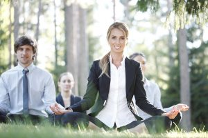 Business people practicing yoga ountoors in park, break relaxaion concept